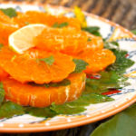 thinly silced Satsuma oranges on a plate with fresh herbs