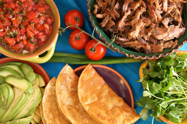 Ingredients for Pulled Pork Pickled Tomato Tacos on a blue cloth.