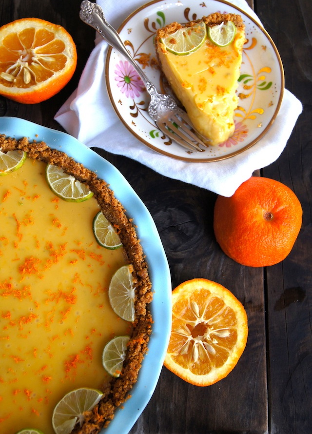 Seville Orange-Key Lime Pie with Cardamom Crust in a light blue pie plate with one slice on a floral plate and a couple of the oranges cut in half