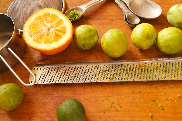 zested limes and half of a Seville orange with measuring spoons and zester for Seville Orange-Key Lime Pie with Cardamom Crust