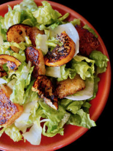 Close up of Fried Lemon Caesar Salad on a red plate