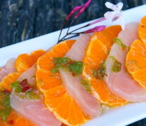 Spicy Yellowtail and Mandarin Sashimi on a white, narrow plate with pink flowers and grated jalapeno.