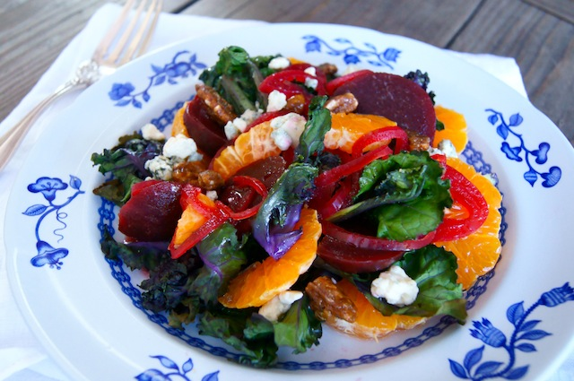 Roasted Kale Sprout Salad with Pickled Beets and Mandarines on a white plate iwth blue flowers