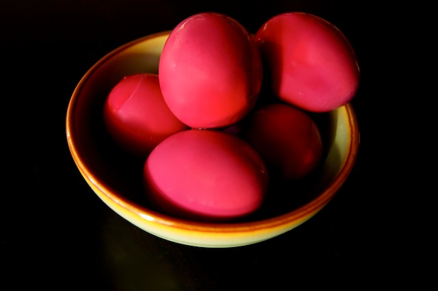 Several whole beet pickled eggs in a light green bowl