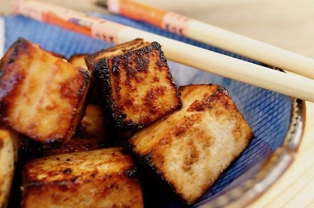 Close up of Miso Garlic Ginger Tofu cubes in a bright blue bowl with chop sticks