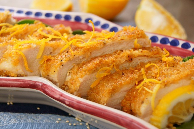 sliced quinoa crusted chicken on platter with lemon
