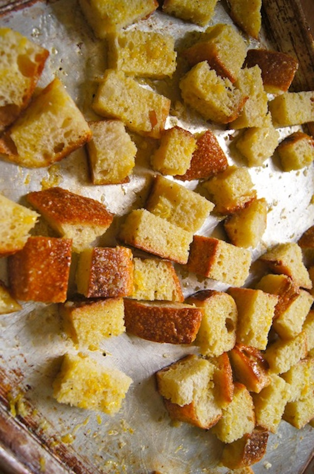 Marinated Lemon-Garlic Roasted Croutons on a sheet pan prepearing for the oven.