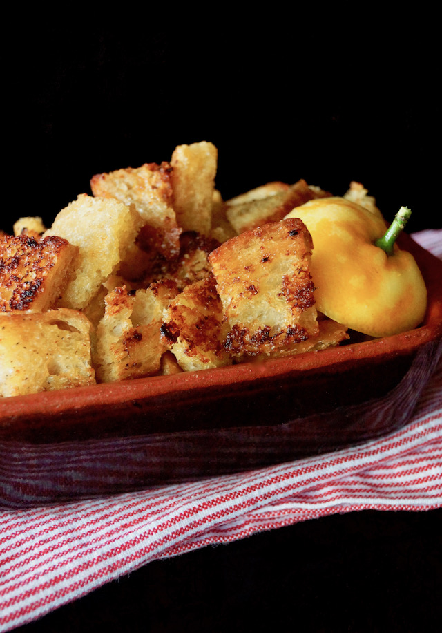Lemon Garlic Roasted Croutons in a brown ceramic dish.