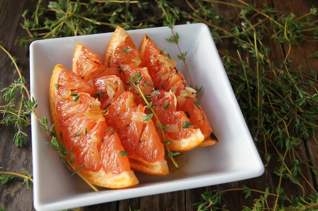 Broiled Grapefruit Slices with honey in a square white dish with dozens of fresh thyme sprigs around it