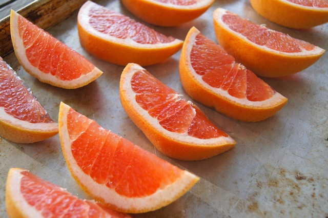 fresh pink-colored grapefruit wedges on a baking sheet