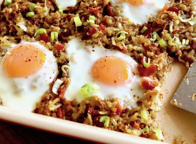 Bacon Hash Brown Casserole with fried eggs on top and slice removed