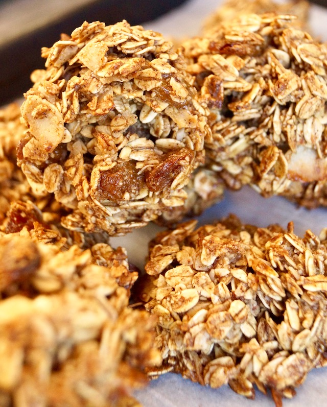 Pile of granola breakfast cookies on parchment paper.