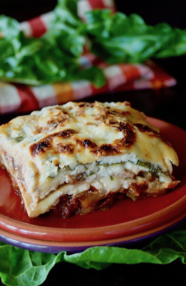 Slice of gluten-free, vegetarian Swiss Chard Lasagna on a red plate.