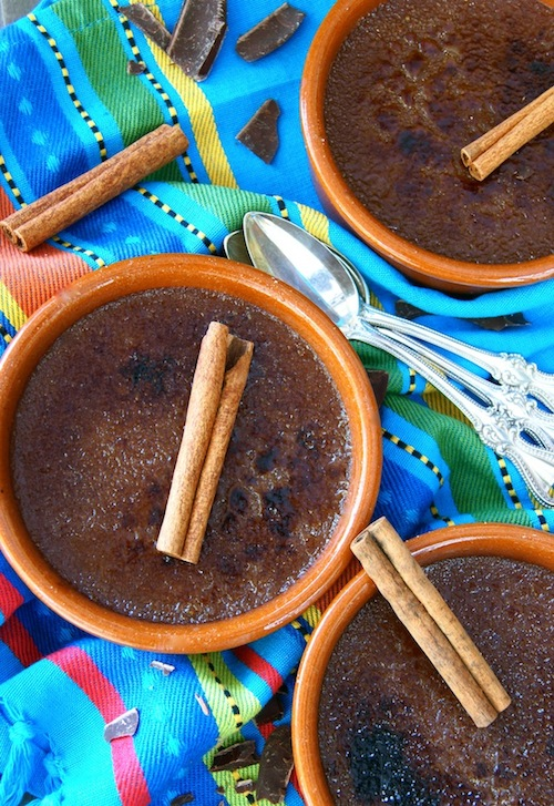 Three Mexican Chocolate Creme Brulee in terra cotta ramekins with cinnamon sticks