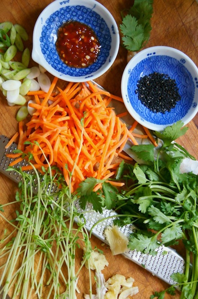 Carrots, ginger, scallions, cilantro, black sesame seeds, chili paste forfor Sesame Chicken Shirataki Noodle Stir Fry Recipe, on a wooden cutting board.