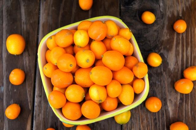 bowl full of kumquats on wooden surface