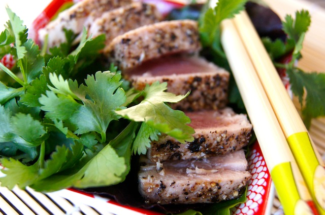 Thinly sliced Kampot Pepper Seared Ahi Tuna with fresh cilantro and chopsticks.