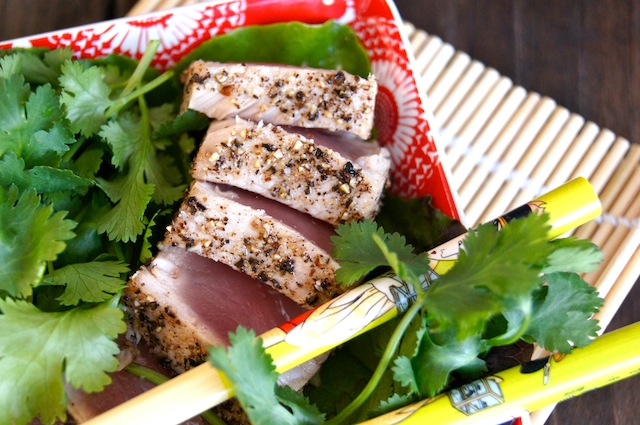 Thinly sliced Kampot Pepper Seared Ahi Tuna onr a red plate with a lot of cilantro and yellow chopsticks.