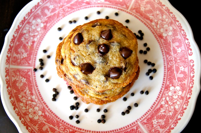 Kampot Black Pepper Chocolate Chip Cookies on a red-rimmed plate with peppercorns surrounding it.