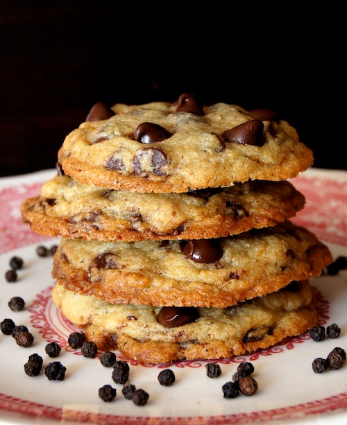 Stack of 4 Kampot Black Pepper Chocolate Chip Cookies on a white and red plate with peppercorns.