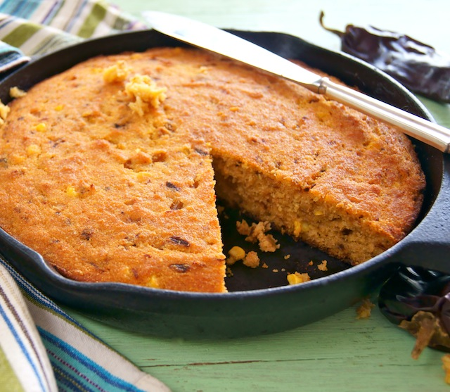 Gluten-Free Hatch Chile Skillet Cornbread in a cast iron skillet with a knife on top.