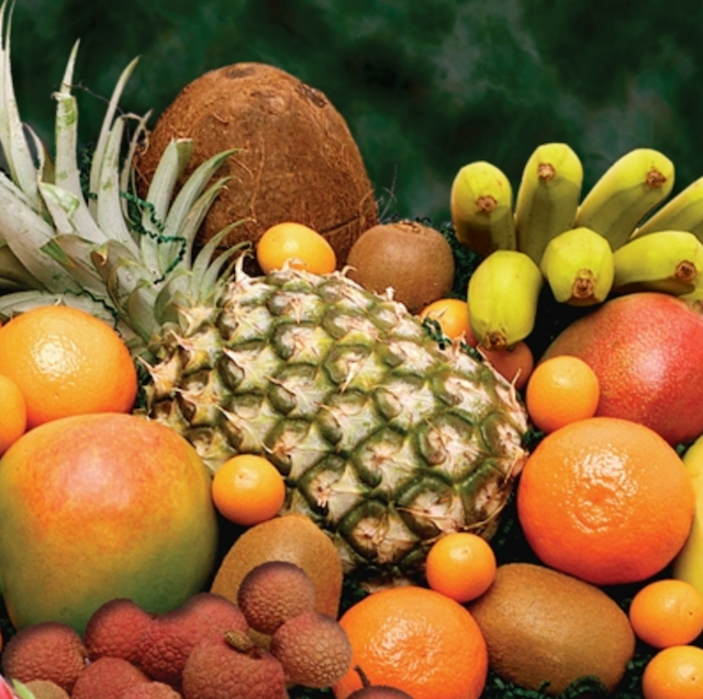Pile of exotic fruits including pineapple, bananas, oranges, mangoes, lychees and coconuts.