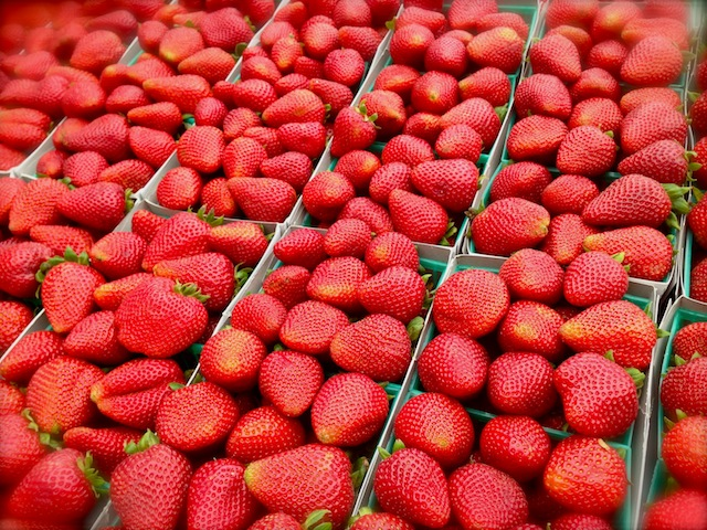Several green baskets of fresh strawberries.