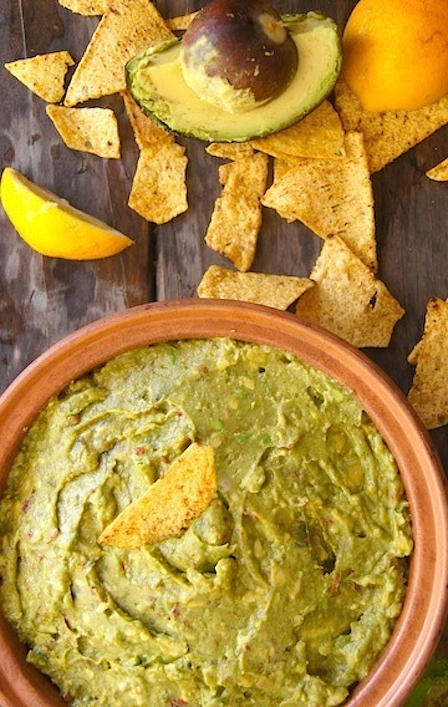 Smoky Lemon Chipotle Guacamole Recipe in a large teracotta bowl with one chip in the middle, on a wooden table.