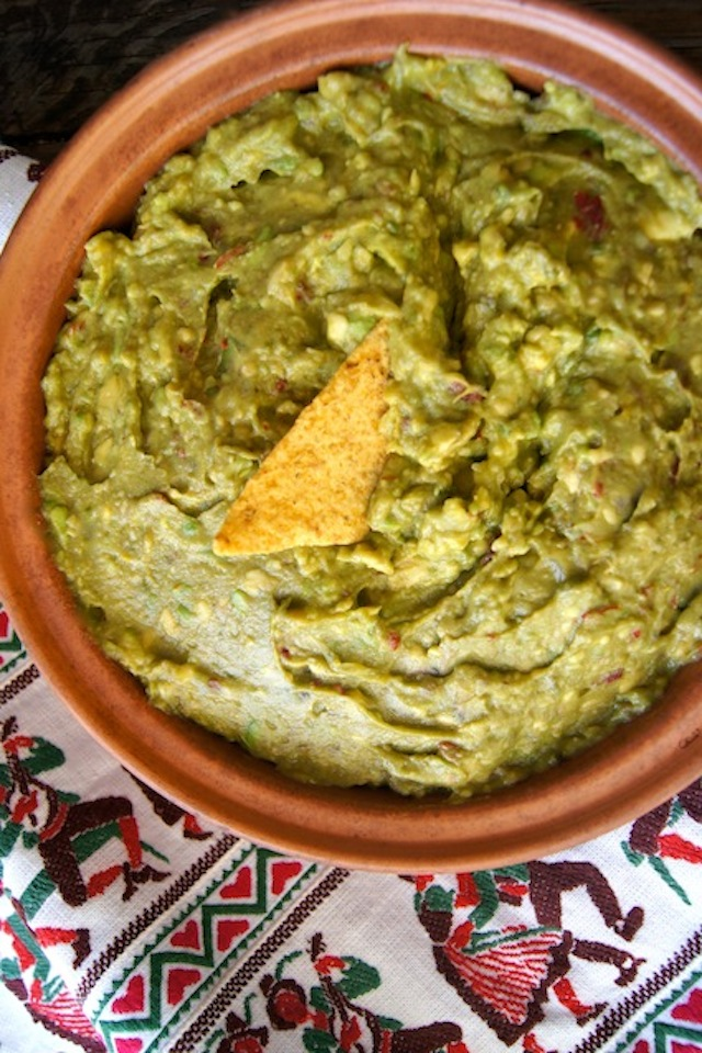 Chipotle Lemon Guacamole Recipe in a terra cotta bowl with a chip in the center
