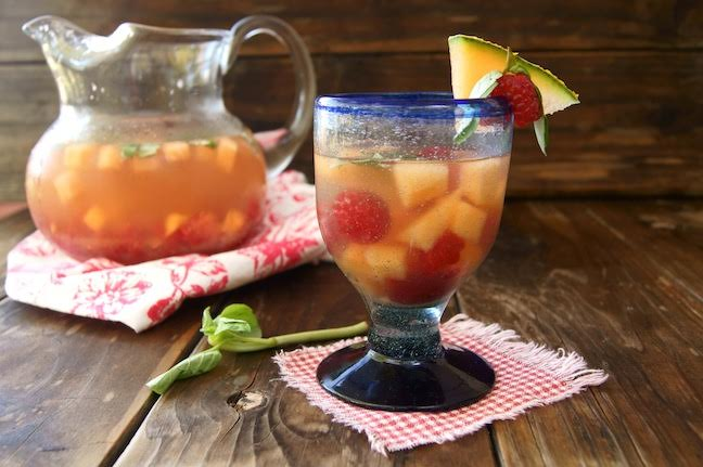 Melon Sangria in a wine glass with a large glass pitcher behind it, on dark wood background.