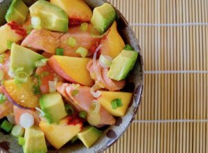 Avocado Salmon Bowl with Peaches in ceramic bowl on sushi mat