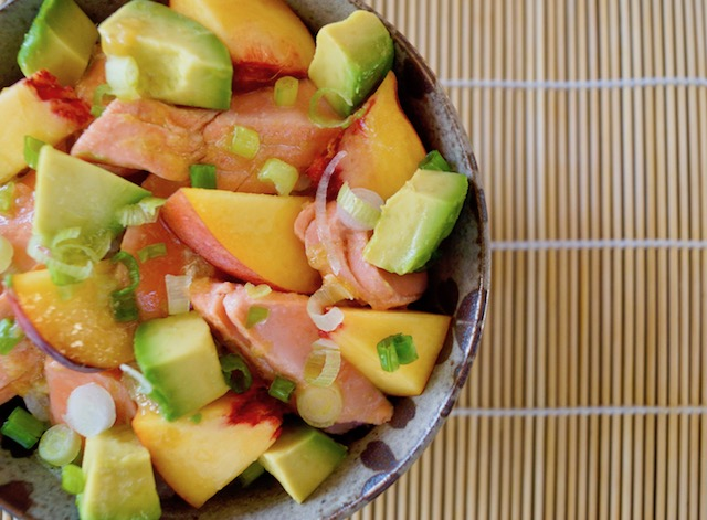 Sockeye Salmon Recipe with Peaches and Avocado in ceramic bowl on sushi mat