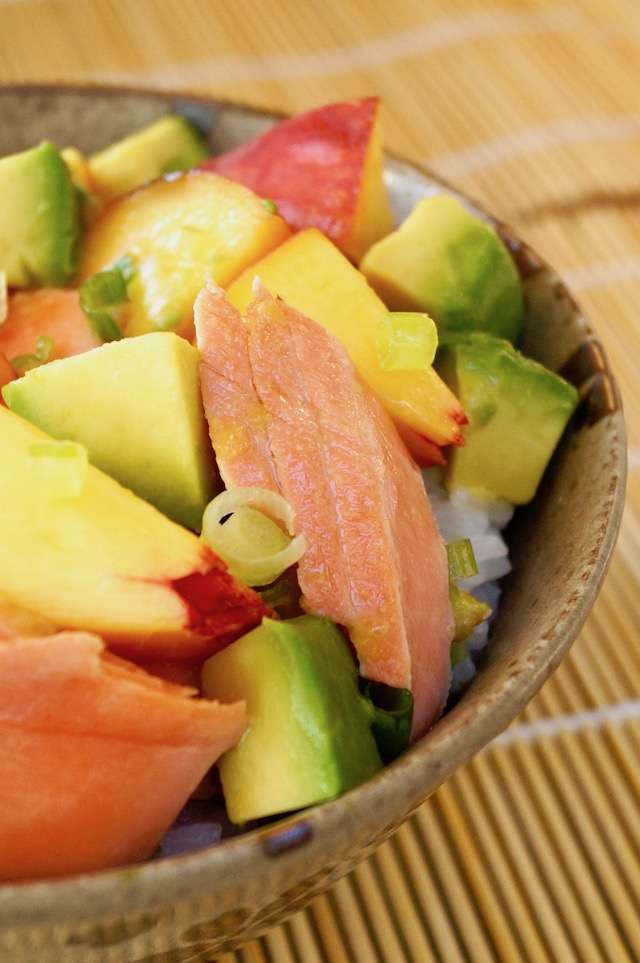 close up of Sockeye Salmon Recipe with Peach and Avocado in ceramic bowl on sushi mat