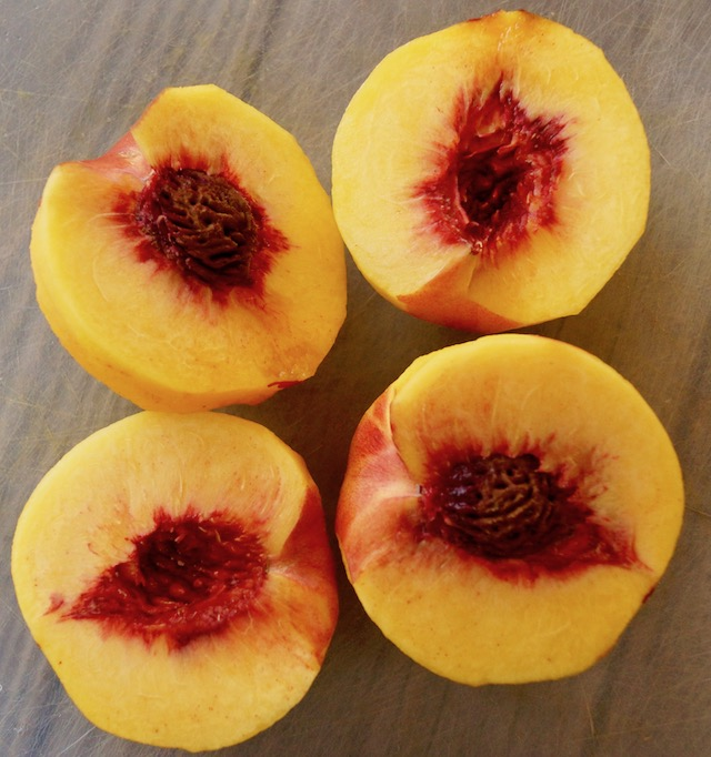 halved peaches on cutting board