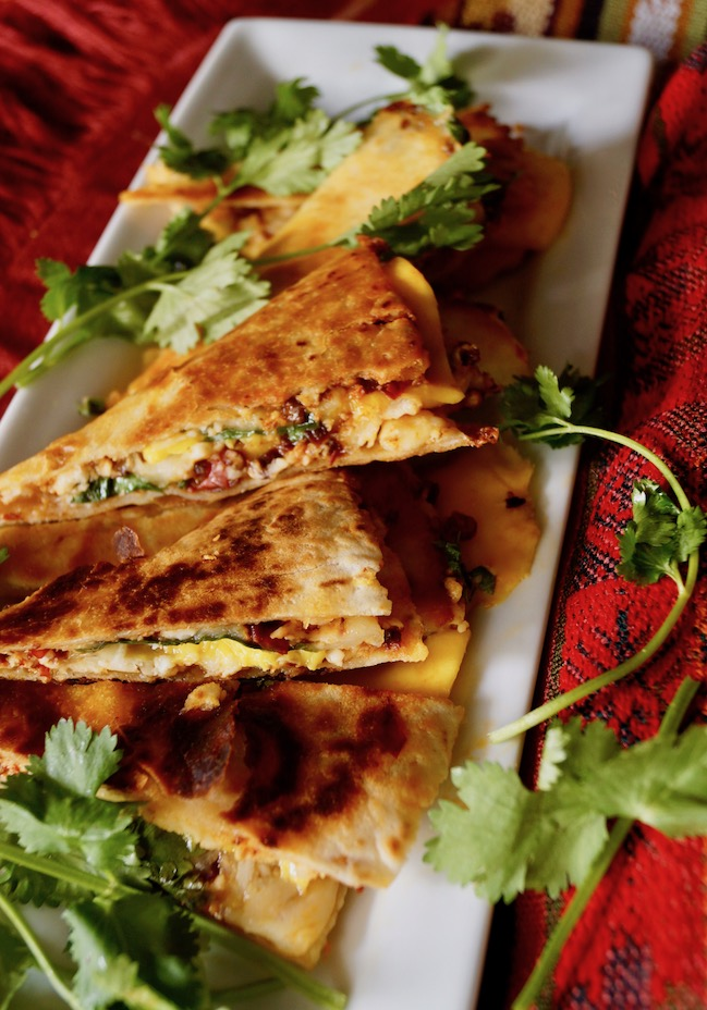 Small slices of Chipotle Mango Quesadillas on a narrow white plate.