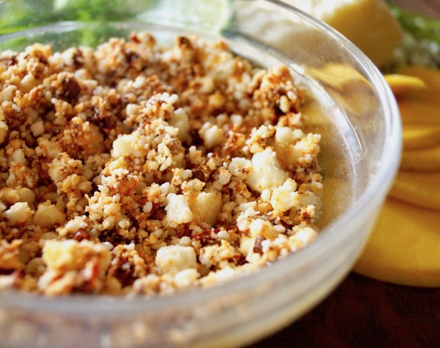 crumbled cotija cheese mixed with chipotles in a glass bowl