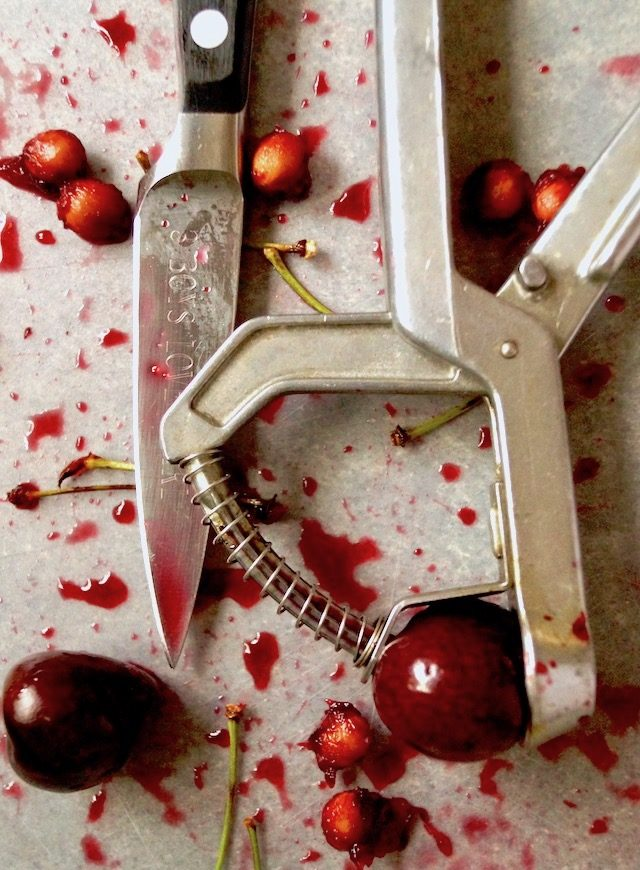 a few cherries, pits and stems with juice and cherry pitter