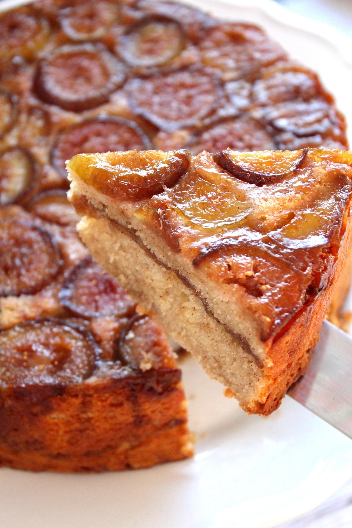 Fig cake with one slice being llifted from whole cake