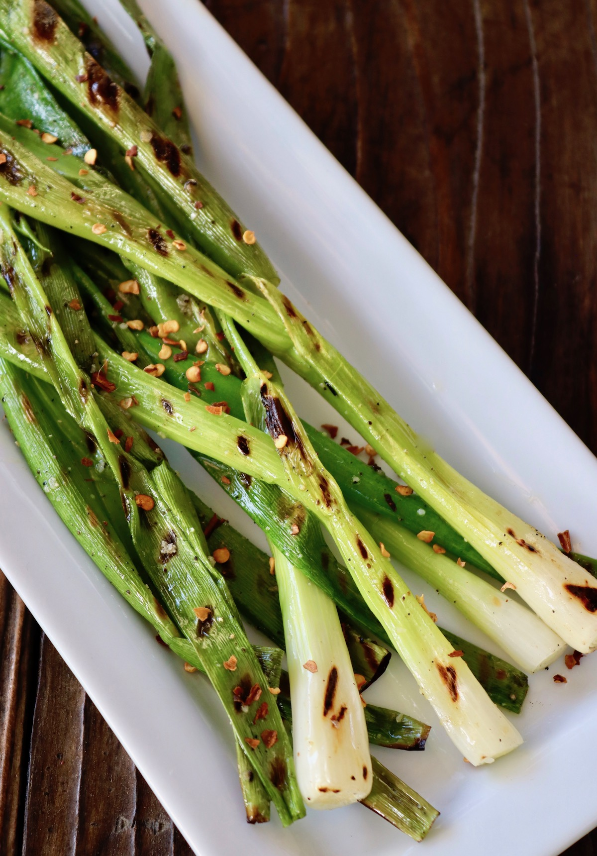Grilled Green Onions on a narrow white plate