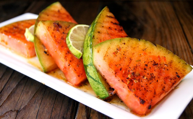 Chile-Lime Grilled Watermelon on a white long plate with a dark wooden background.