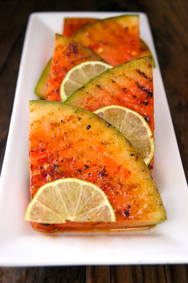 Chile-Lime Grilled Watermelon slices with lime on a narrow white plate.
