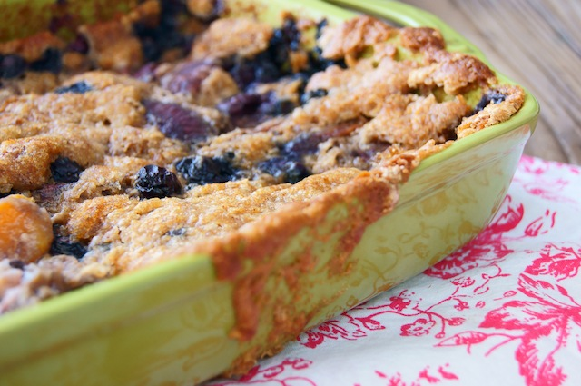 Gluten-Free Chai Spiced Peach-Blueberry Cobbler with a golden topping, spilling over the side, in a green baking dish.