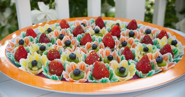 Fresh Fruit Tartlets with strawberries, kiwi and blueberries on orange platter.