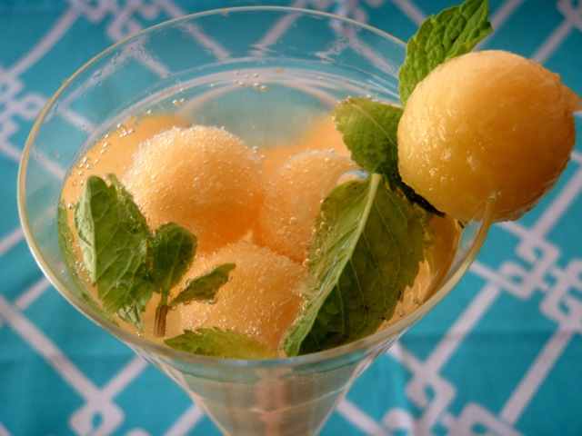 Melon Proseco in a martini glass with fresh mint and a melon ball of the rim.