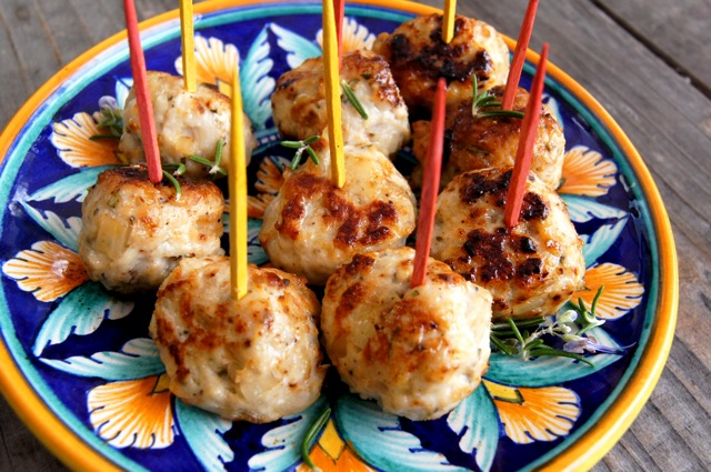 Rosemary Honey Turkey Meatballs on a pretty blue and gold plate with red and yellow toothpicks in them.