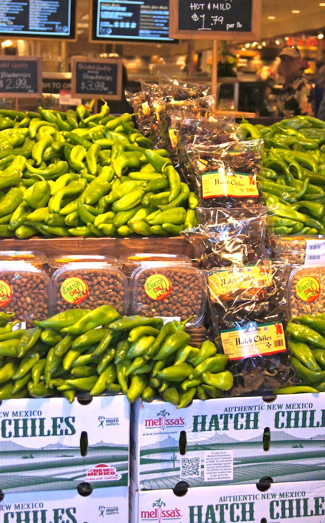 Piles of fresh Hatch Chiles and a row of bags of dried Hatch Chiles.