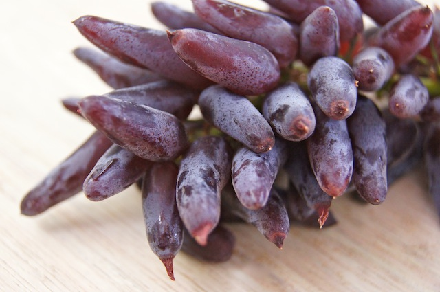 1 bunch of Witch Fingers Grapes on a light surface.