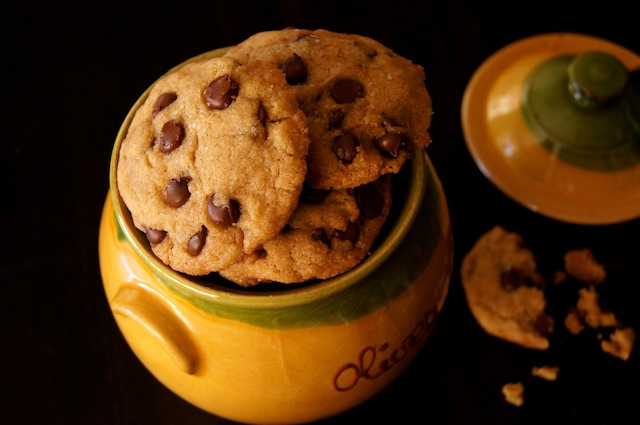 A gold, ceramic jug overflowing with Olive Oil Chocolate Chip Cookies.