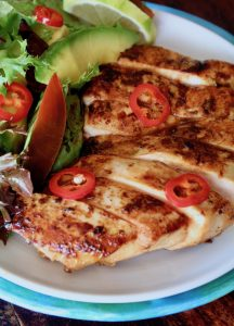 sliced tequila lime chicken with a salad on a white plate