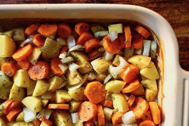 Chopped raw potatoes, carrots and onions in baking dish.